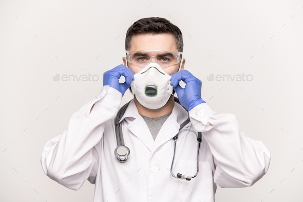 Contemporary clinician in whitecoat, gloves and eyeglasses putting respirator - Stock Photo - Images