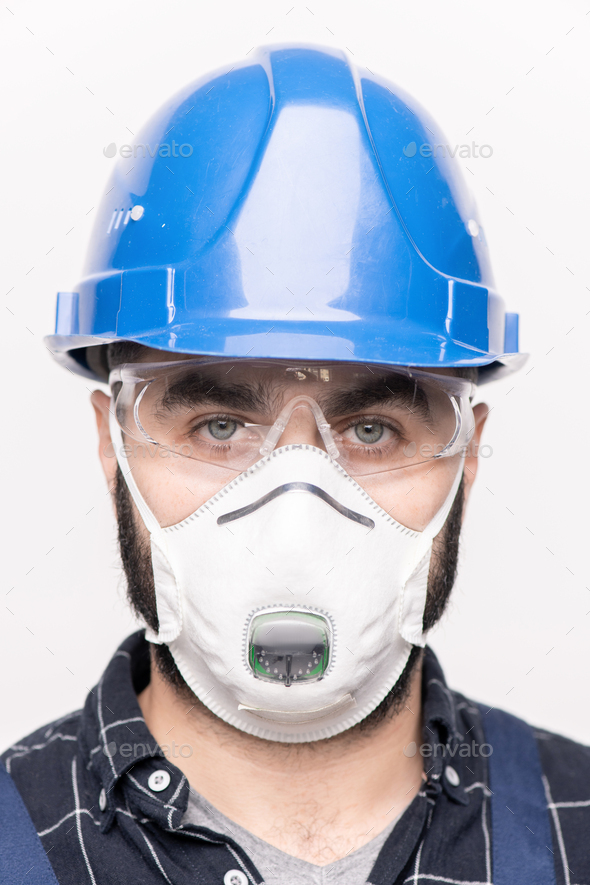 Head of young engineer or builder in hardhat and protective mask looking at you - Stock Photo - Images