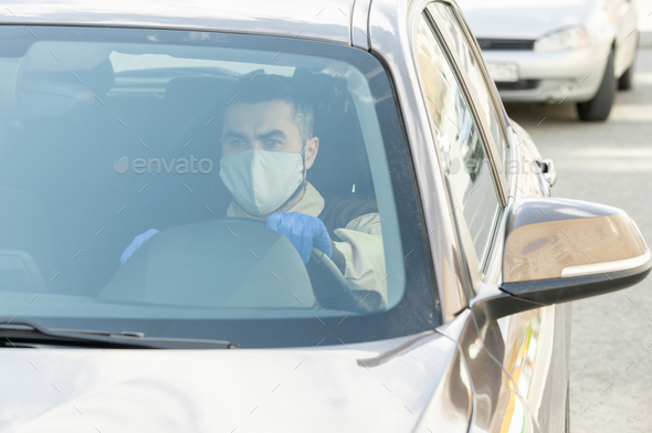 Young serious courier in protective mask and gloves driving to clients - Stock Photo - Images