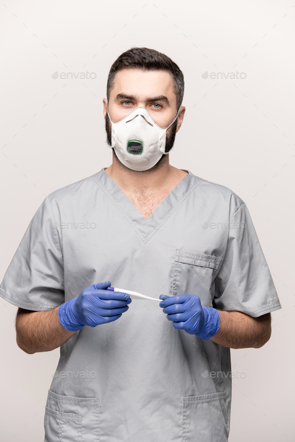 Contemporary doctor in uniform, protective gloves and respirator looking at you - Stock Photo - Images