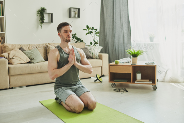 Calm guy in activewear standing on his knees with hands put together by chest - Stock Photo - Images