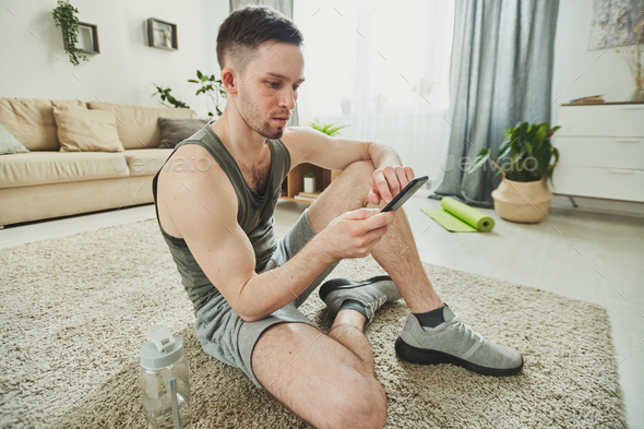 Young sweaty athlete sitting on the carpet and scrolling through messages - Stock Photo - Images