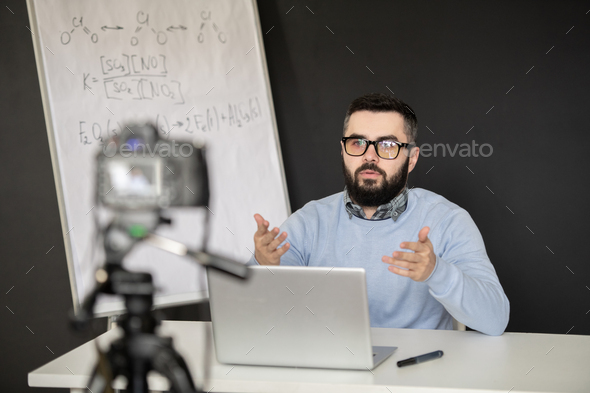 Contemporary school teacher in pullover and eyeglasses explaining formula - Stock Photo - Images