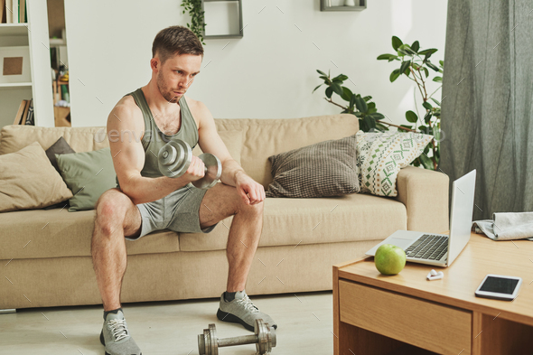 Young man in sportswear sitting on couch in front of laptop while exercising - Stock Photo - Images