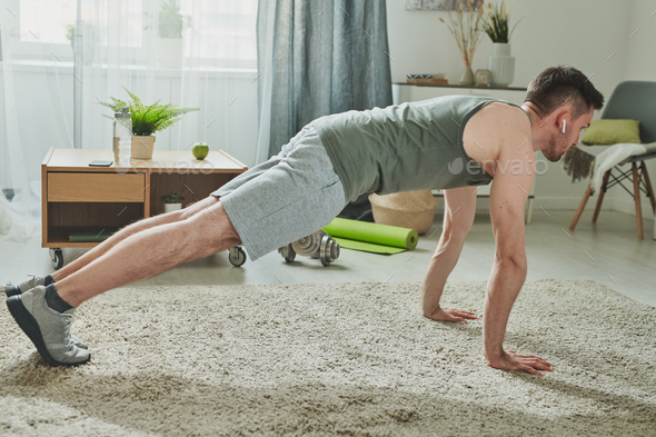 Young man in sportswear and earphones doing press-ups in living-room - Stock Photo - Images