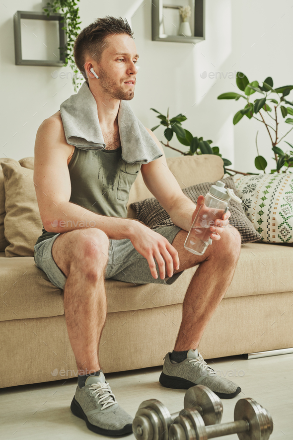 Tired athlete in sportswear listening to music in earphones and having water - Stock Photo - Images