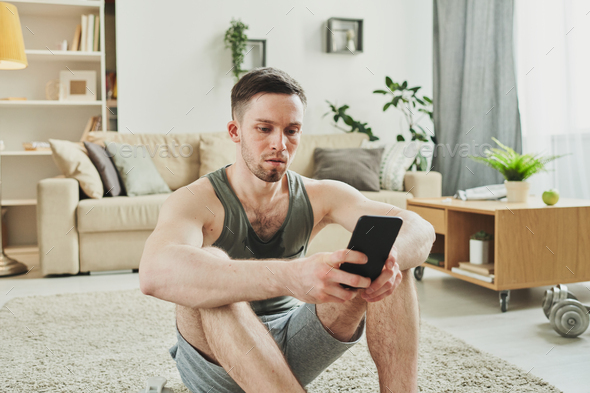 Young serious sportsman in activewear sitting on the carpet in living-room - Stock Photo - Images