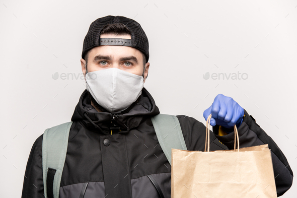 Young handome man in casual jacket, cap, protective mask and gloves - Stock Photo - Images
