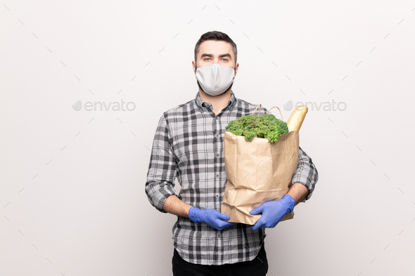 Serious young man in protective mask and gloves delivering fresh food products - Stock Photo - Images