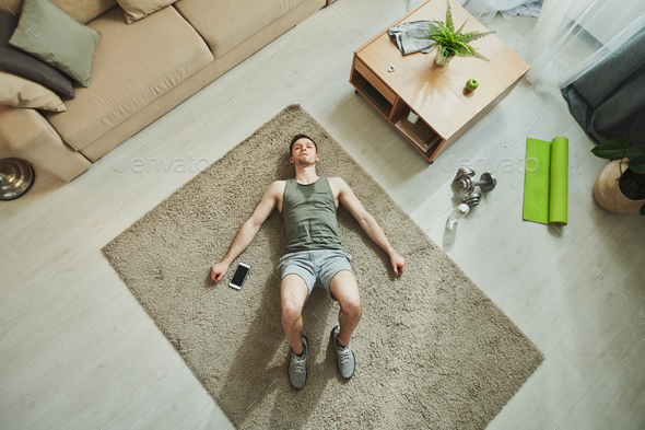 Overview of young tired muscular man in sportswear relaxing in living-room - Stock Photo - Images