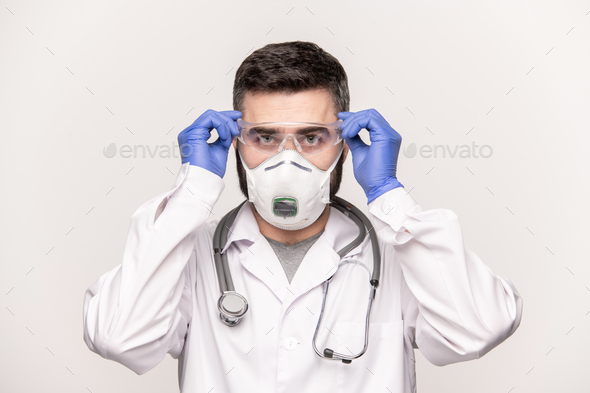 Contemporary young doctor in whitecoat, protective gloves and respirator - Stock Photo - Images