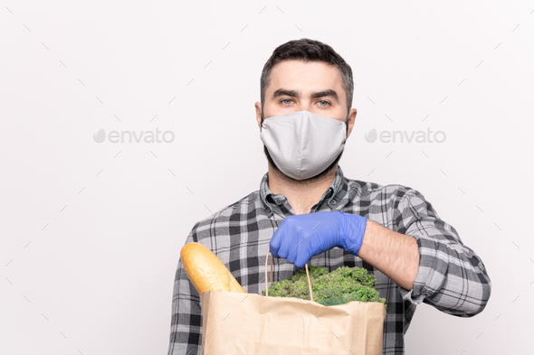Young courier in protective mask and gloves delivering fresh bread and vegs - Stock Photo - Images