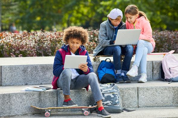 Children using gadgets outdoors - Stock Photo - Images