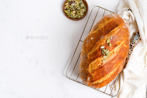 Freshy baked homemade bread with pumpkin seed on a light grey marble table decorated textile towel - Stock Photo - Images