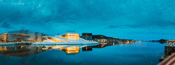 Oslo Norway. Evening View Of Illuminated Opera Ballet House Among High-Rise Buildings Under Blue Sky - Stock Photo - Images