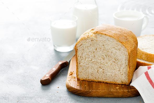 Homemade white wholegrain bread sliced on wooden board - Stock Photo - Images