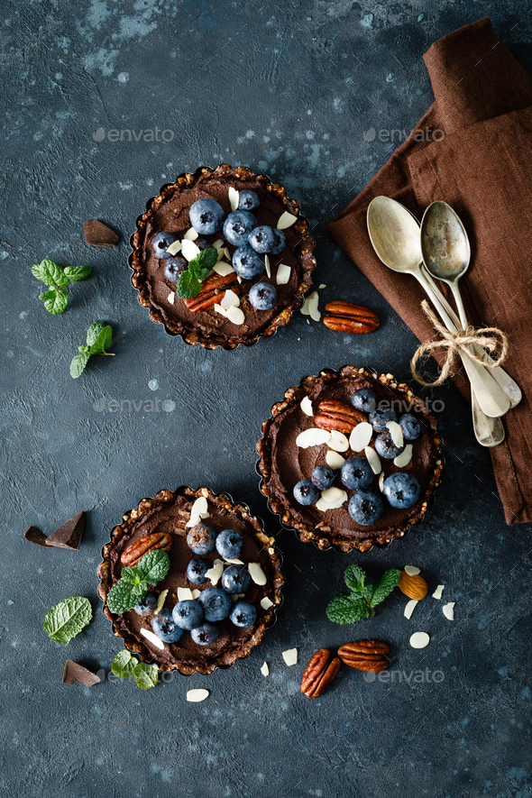 Healthy raw vegan dessert dates tartlets with chocolate cream - Stock Photo - Images