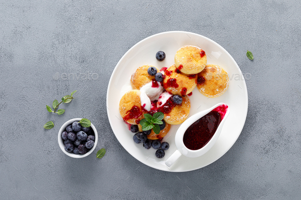 Baked cottage cheese pancakes, syrniki with yogurt, blueberry sauce and fresh berries - Stock Photo - Images