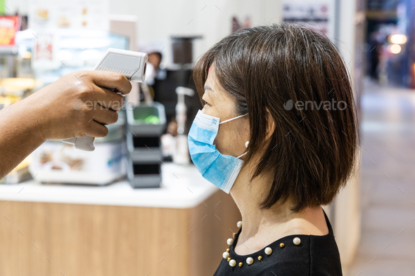 New normal requiring shopper wear mask and scan with thermometer for temperature before admittance - Stock Photo - Images