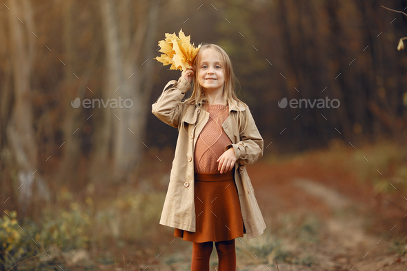Cute little girl walks in a autumn park - Stock Photo - Images