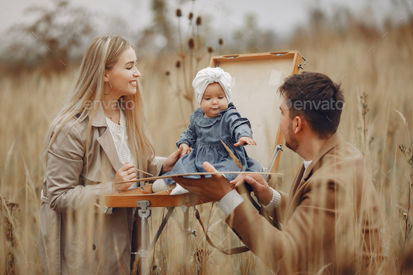 Family with little daughter painting in a autumn field - Stock Photo - Images