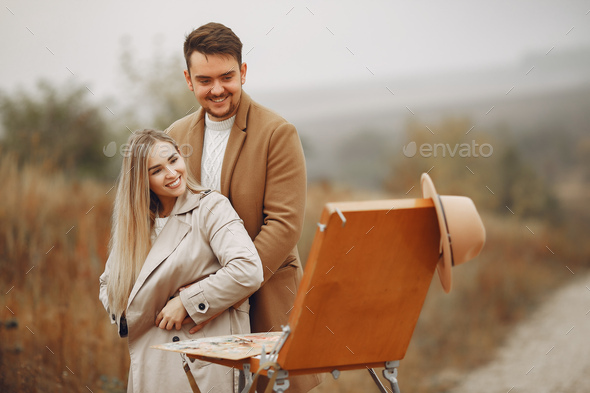 Elegant couple painting in a autumn field - Stock Photo - Images