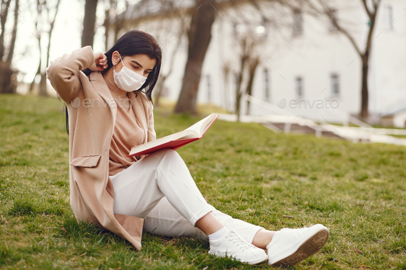 Woman in a mask sitting on a grass - Stock Photo - Images