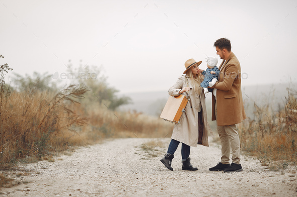Stylish family walking on a autumn field - Stock Photo - Images
