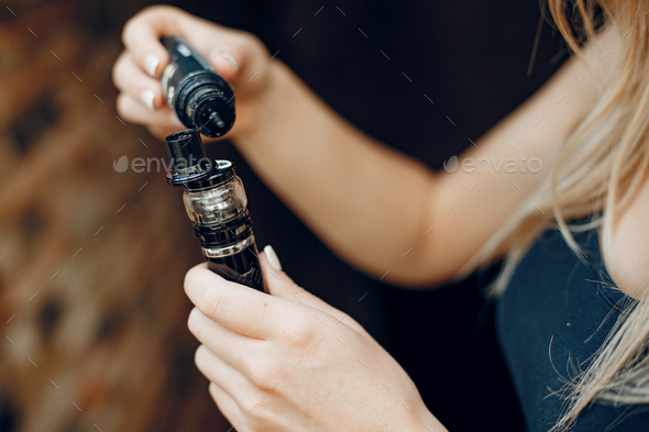Stylish young girl in a city with vape - Stock Photo - Images