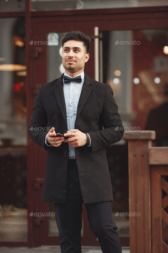 Stylish businessman in a black suit standing outside - Stock Photo - Images