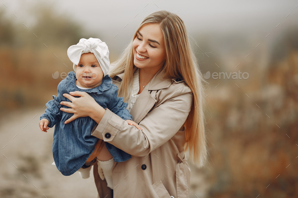 Mother with daughter playing in a autumn field - Stock Photo - Images