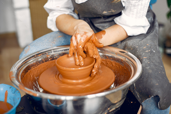 Girl making a vaze from a clay on a pottery's machine - Stock Photo - Images