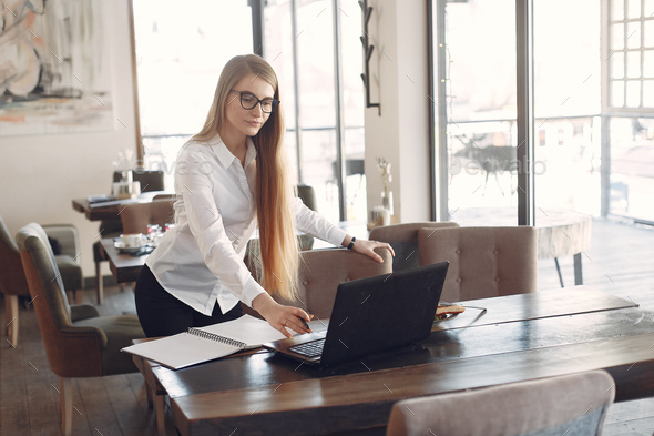 Businesswoman sitting at the table with a laptop - Stock Photo - Images