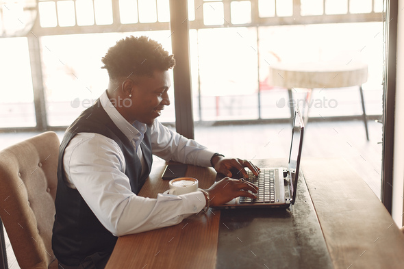 Black man sitting in a cafe and drinking a coffee - Stock Photo - Images