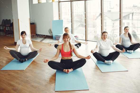 Pregnant women doing yoga with a coach - Stock Photo - Images