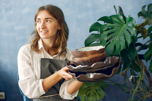 A young woman holds a ceramics dish in her hands - Stock Photo - Images