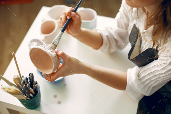 A young woman mpainting dishes in a pottery - Stock Photo - Images