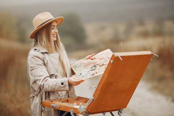 Woman in a brown coat painting in a field - Stock Photo - Images
