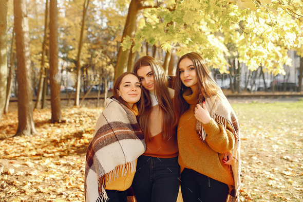Elegant and stylish girls in a autumn park - Stock Photo - Images