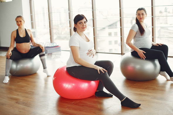 Pregnant women doing yoga in a gym - Stock Photo - Images