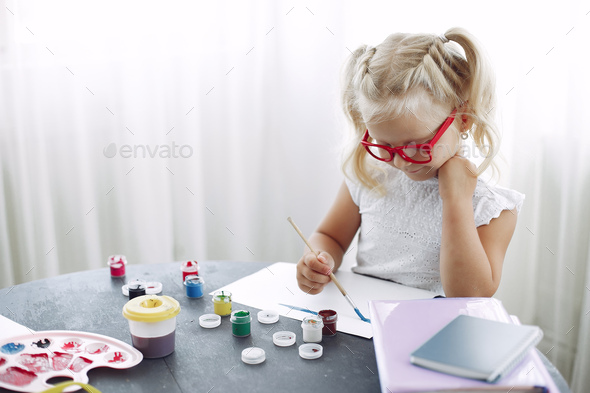 Little girl sitting on a table and drawing - Stock Photo - Images