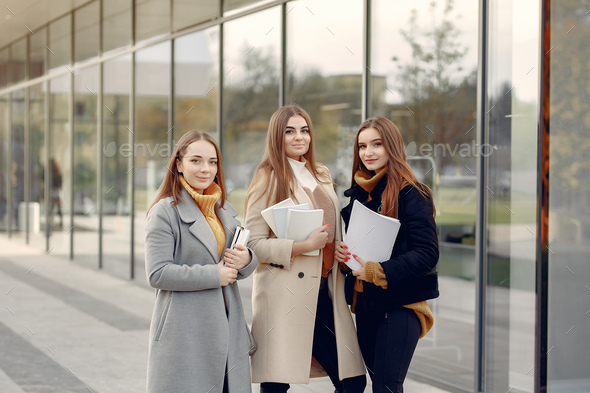 Young students on a student campus standing with a documents - Stock Photo - Images