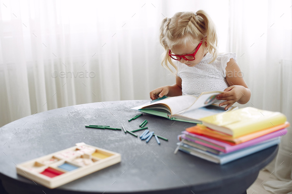 Little girl sitting on a table with books - Stock Photo - Images