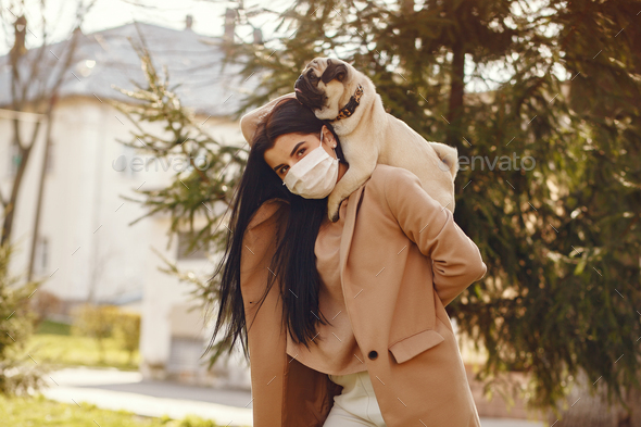 Brunette in a mask walks with pug - Stock Photo - Images