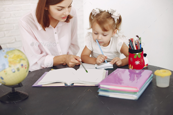 Tutor with litthe girl studying at home - Stock Photo - Images