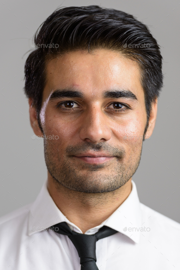 Young handsome Persian man against white background - Stock Photo - Images