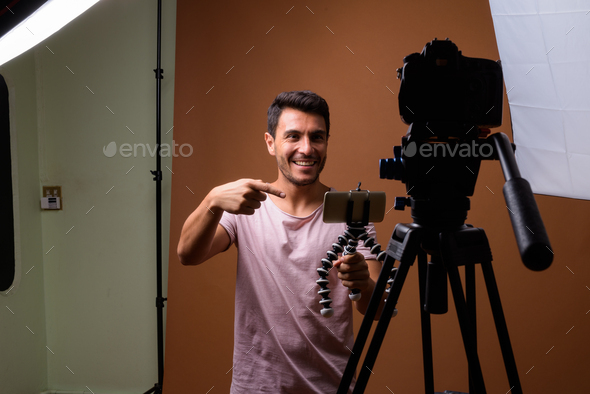 Young handsome Hispanic man against brown background - Stock Photo - Images
