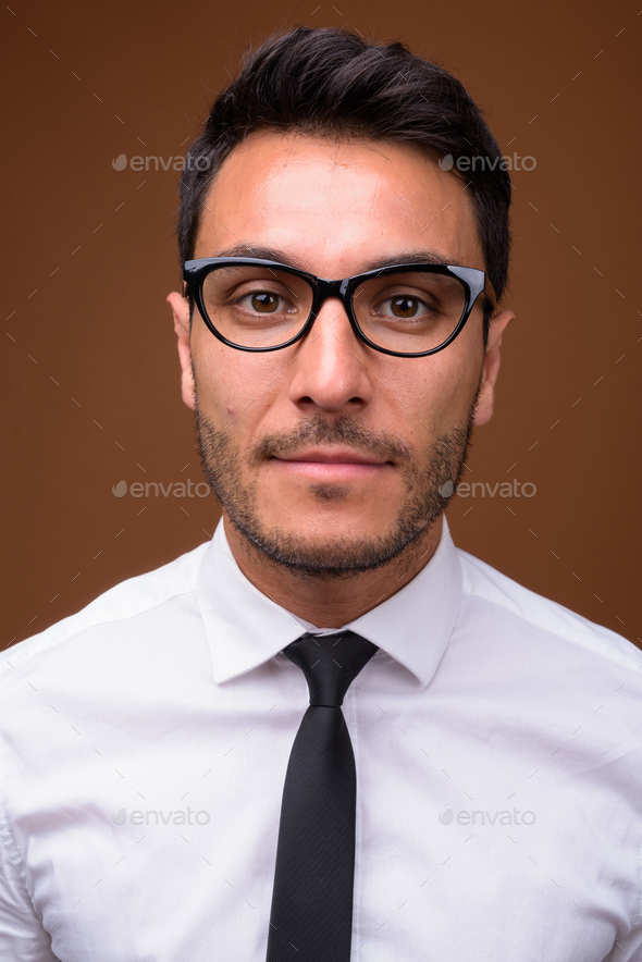 Young handsome Hispanic businessman against brown background - Stock Photo - Images