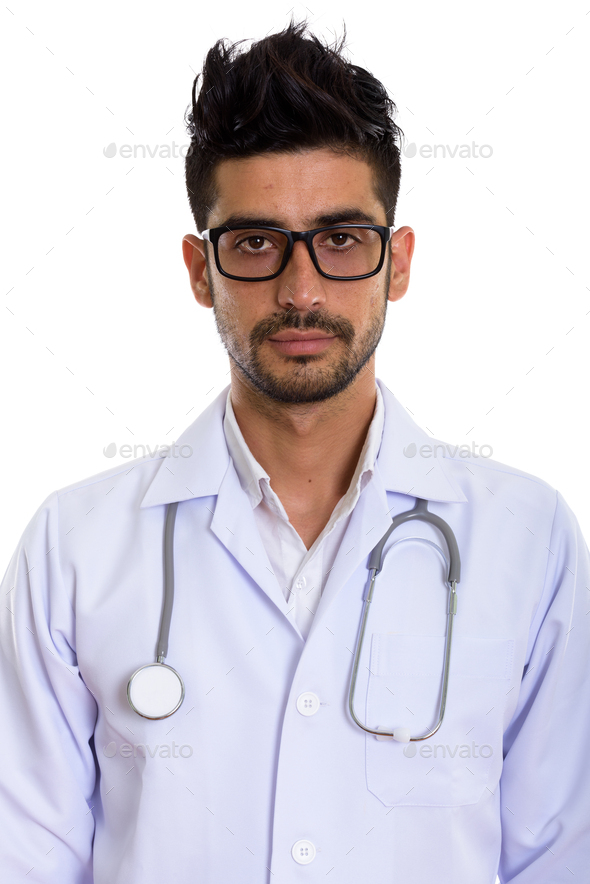 Young handsome bearded Persian man doctor with eyeglasses - Stock Photo - Images