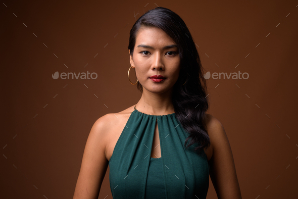 Studio shot of beautiful Asian businesswoman in green dress - Stock Photo - Images